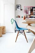 Blue Eames chair in modern study with wooden furniture and mood board