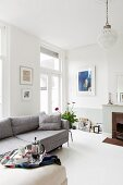Grey sofa and fireplace in bright, modern living room in period building