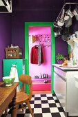Purple wall, turquoise metal locker and green door frame in small kitchen with chequered floor and view into pink hallway