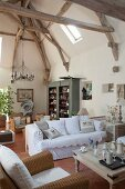 Exposed wooden roof structure above wicker armchairs and and white, loose-covered sofa in open-plan interior