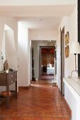 Rustic hallway with terracotta floor tiles and white walls