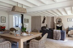 Wicker furniture in open-plan living-dining area of renovated farmhouse