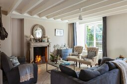 Open fireplace, classic upholstered furniture and exposed ceiling beams in living room