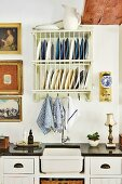 Vintage plate rack and gilt-framed pictures above retro sink in black worksurface