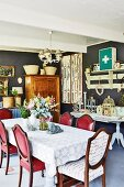 Antique chairs with red upholstery, shelves with hooks above console table and cabinet in background in vintage dining room