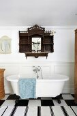 Antique wall-mounted cabinet made from dark wood above clawfoot bathtub and black and white rug on chequered tiled floor