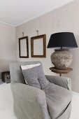 Grey armchair next to rustic table lamp on side table in front of empty picture frames on wall painted pale grey