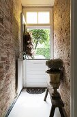 Plant in antique urn on rustic bench in narrow hallway with exposed brick walls leading to stable door with open top half