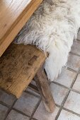 Pale sheepskin blanket on wooden bench