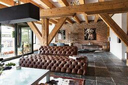 Brown leather sofa in loft-style interior with exposed, solid wooden beams
