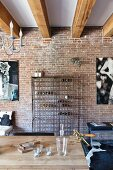 Metal wine rack against brick wall and wooden table in interior with wood-beamed ceiling