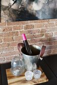 Bottle in wine cooler and tealights on wooden board in front of brick wall
