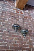 Oriental lanterns hanging from wooden beam against brick wall