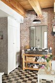 Bathroom with chequered floor, brick wall and washstand with trough-style sink on wooden frame