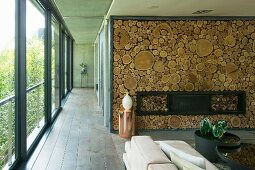 Cylindrical copper table in front of fireplace in wall decorated with slices of tree trunks and next to hallway with glass wall
