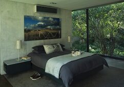Large artwork above double bed flanked by shimmering, pearl-coloured lamps on bedside cabinets