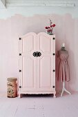 Pink-painted farmhouse wardrobe with black wrought iron fittings in pink interior