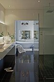 Spotlights in ceiling, mirrored cabinet with indirect lighting and chandelier above bathtub in modern bathroom with walk-in shower