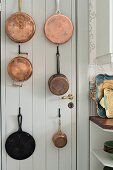 Copper pans hung on white-painted wooden door