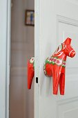 Door handle made from red-painted wooden horse