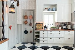 Copper pans hung on door next to white, country-house-style kitchen counter and wall units