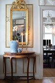 Antique, semicircular console table below gilt-framed mirror on wall next to open door