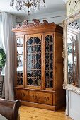 Antique, carved wooden cabinet with glass door panels in traditional interior