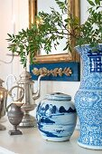 Antique silver jugs, blue and white china pot and vase on shelf below gilt-framed mirror on wall