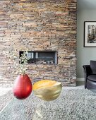 Flowering branches in red vase and gold dish on glass table in front of fireplace in stone-clad chimney breast