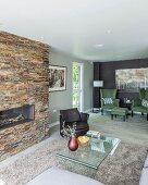 Glastisch auf hellgrauem Teppich, gegenüber Natursteinwand mit eingebautem Kamin, im Hintergrund Sitzbereich mit grünen Sesseln in offenem Wohnraum