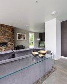 Minimalistischer Glastisch mit Schalen an Rückseite eines grauen Sofas in modernem Wohnraum