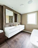 Elegant bathroom painted pale brown with large floor tiles and long, white washstand on wall
