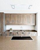Blick über Theke mit eingebautem Glaskeramikherd auf Küchenzeile aus Massivholz