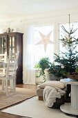 Simply decorated Christmas tree between cable-reel table and dining table