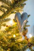 Linen heart hanging from illuminated Christmas tree