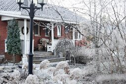 Brick house with veranda in wintry garden covered in hoar frost