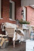 Fur blanket on wicker armchair on veranda of brick house