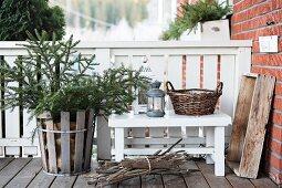 Fir tree in wooden basket next to lantern on bench on veranda