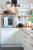 Cosily lit kitchen with storage jars on open-fronted shelves