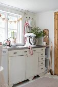 Mixer and vase of fir branches on festively decorated kitchen counter below garland of gingerbread hearts