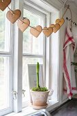 Amaryllis in decorative pot on windowsill below garland of gingerbread hearts threaded on cord