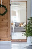 Christmas wreath on open wooden door with view of couch in living room