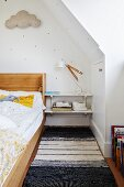 Wood.framed bed, bedside shelves and blac and white rug in child's attic bedroom