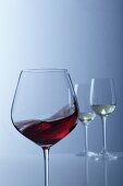 Red wine swirling in a glass with two glasses of white wine in the background