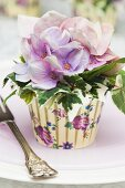Silk flowers and ivy in colourful paper cake cases decorating table