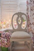 Antique, Swedish wooden chair flanked by vase of hydrangeas and floral curtain; tealights and roses on windowsill in background