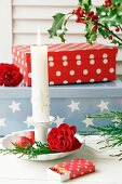 Advent arrangement of candlestick, rose, matchbox covered in wrapping paper and gift box in background