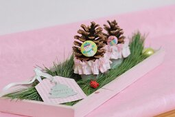 Festive table arrangement of gift tag and pine cones on pink tray