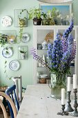 Candlesticks and blue flowers in glass jar on wooden table in front of display case and decorative wall plates on pale green wall