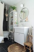 Simple washstand below round mirror on white-tiled wall in bathroom with bathtub behind curtain